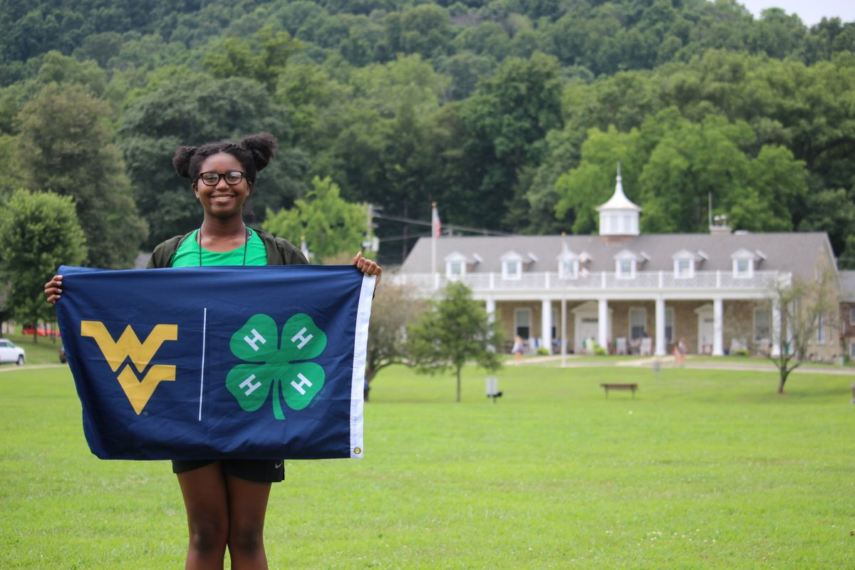 A girl with a flying WV/4-H flag stands on the grounds of WVU Jackson's Mill